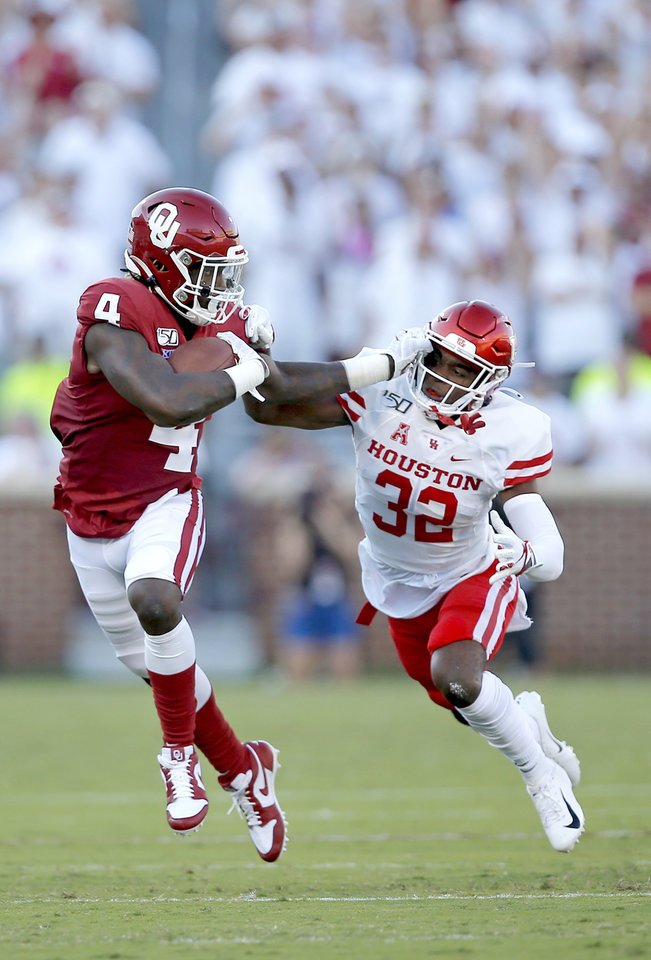 Photo - Oklahoma's Trey Sermon (4) stiff arms Houston's Gervarrius Owens (32) in the first quarter aduring a college football game between the University of Oklahoma Sooners (OU) and the Houston Cougars at Gaylord Family-Oklahoma Memorial Stadium in Norman, Okla., Sunday, Sept. 1, 2019. [Sarah Phipps/The Oklahoman]
