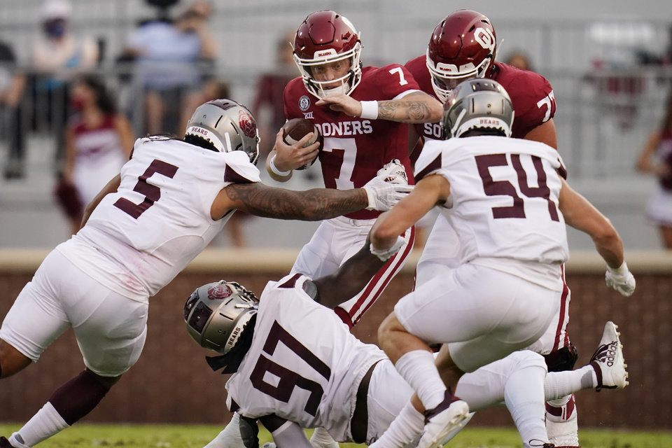 Photo -  OU quarterback Spencer Rattler (7) carries against Missouri State defenders Ferrin Manulelua (5), Michael Pope (97), and Von Young (54) in the first half Saturday in Norman. [AP Photo/Sue Ogrocki]