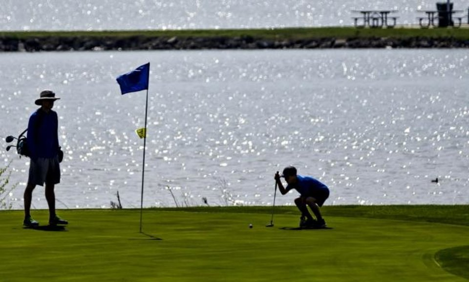 Photo -  Golfers play a round at Lake Hefner Golf Club in Oklahoma City on Friday. [Chris Landsberger/The Oklahoman]