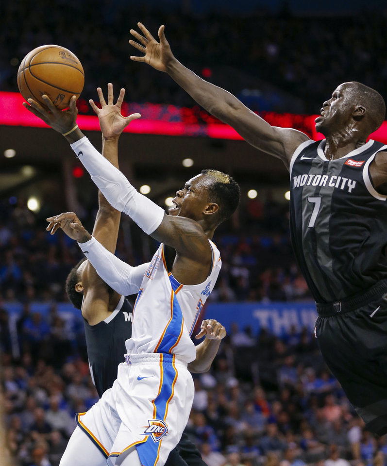 Photo - Oklahoma City's Dennis Schroder (17) tries to get to the basket past Detroit's Thon Maker (7), right, and Ish Smith (14) in the second quarter during an NBA basketball game between the Detroit Pistons and the Oklahoma City Thunder at Chesapeake Energy Arena in Oklahoma City, Friday, April 5, 2019. Photo by Nate Billings, The Oklahoman