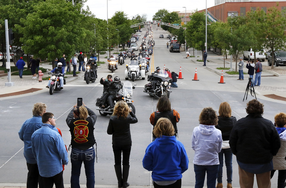 Photo - Onlookers watch and take pictures as the procession of motorcycles continued along NW 5 Street  for about 20 minutes until all participants had arrived at the Oklahoma City National Memorial & Museum. Motorcyclists from across the country, numbering more than 1,000 strong, rumbled through the downtown streets of Oklahoma City on Saturday, April, 22, 2017,  taking part in  the 10th annual Ride to Remember.  The annual benefit run honors the 168 people killed in the April 19, 1995 bombing of the Alfred P. Murrah Federal Building. All funds raised go toward the Oklahoma City National Memorial and Museum, which operates solely on private donations. Bikers rolled out for the first event in 2007.    Photo by Jim Beckel, The Oklahoman
