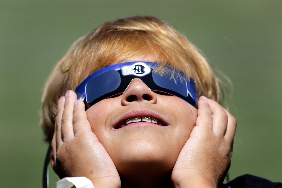 Photo - Zack Logeman 5th grade watches the eclipse at Washington Irving Elementary School in Edmond, Monday August 21, 2017. Zack joined other students, parents and teachers in viewing the eclipse. Photo By Steve Gooch, The Oklahoman