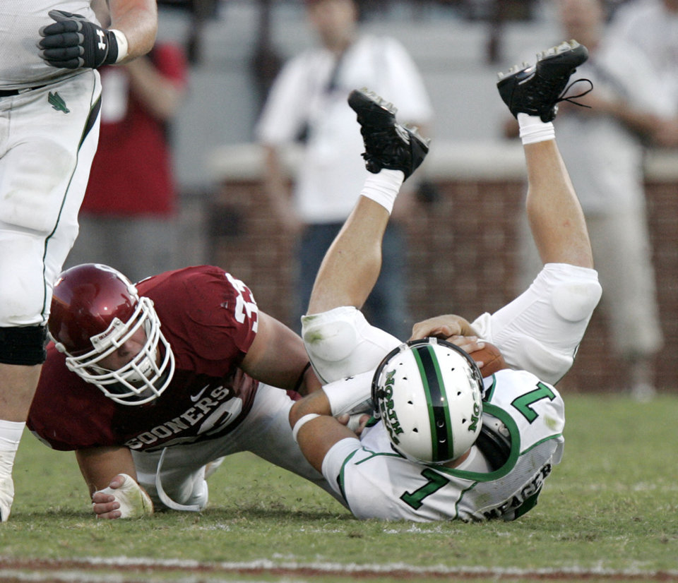Photo - North Texas quarterback Daniel Meager (7) is dropped for a loss by Oklahoma defensive end Auston English (33) in the first half during the University of Oklahoma Sooners (OU) college football game against the University of North Texas Mean Green (UNT) at the Gaylord Family - Oklahoma Memorial Stadium, on Saturday, Sept. 1, 2007, in Norman, Okla.