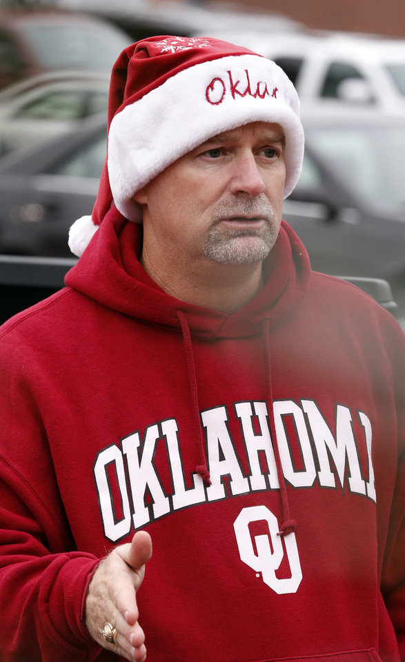 Photo - Fan Jimmy Cordell of Newcastle combines football and Christmas seasons before a Bedlam college football game between the University of Oklahoma Sooners (OU) and the Oklahoma State Cowboys (OSU) at Gaylord Family-Oklahoma Memorial Stadium in Norman, Okla., on Saturday, Dec. 6, 2014. Brody Brown, 4, gets a ride in barrells used for a toss game by his mother Brandi Hokit.  Photo by Steve Sisney, The Oklahoman
