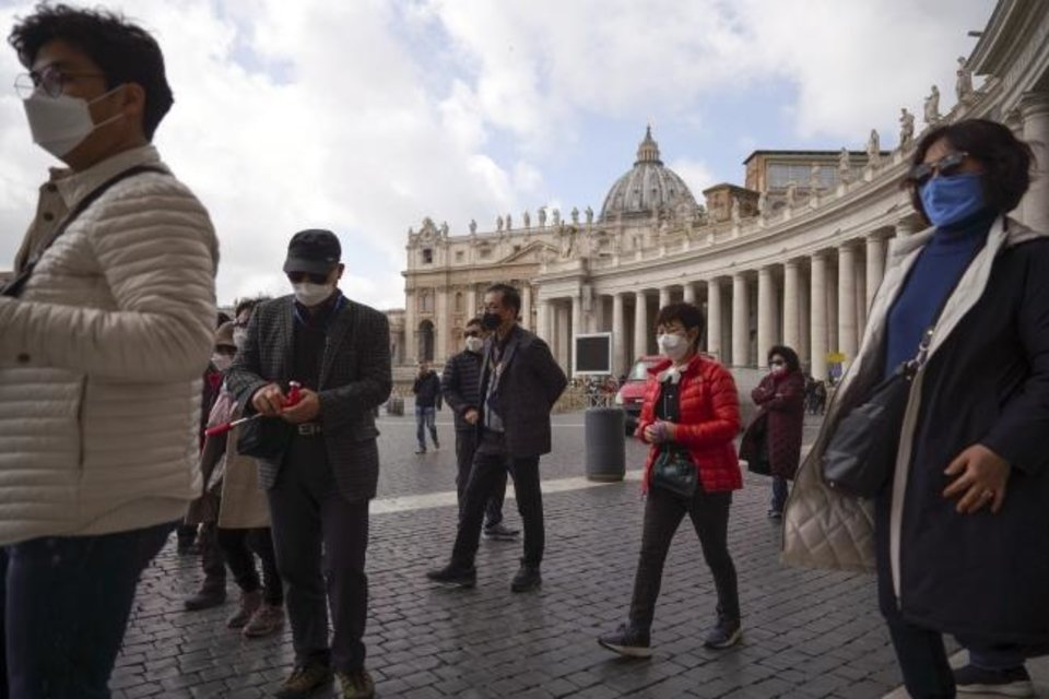 Photo -  Tourists wearing masks take a tour of St. Peter's Square on Friday at the Vatican. A Vatican spokesman has confirmed the first case of coronavirus at the city-state. Vatican spokesman Matteo Bruni said Friday that non-emergency medical services at the Vatican have been closed so they can be sanitized after the positive test on Thursday. [AP PHOTO]