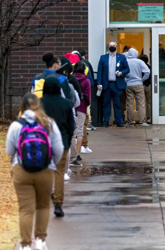 Photo -  Principal Greg Frederick takes temperatures at the door as students wait in line to return to class at U.S. Grant High School in Oklahoma City, Okla. on Tuesday, Nov. 10, 2020. Students in grades first through 12th return to Oklahoma City Public Schools for the first time since March. The school district will have students attend in-person classes twice a week in a hybrid A/B schedule. [Chris Landsberger/The Oklahoman]