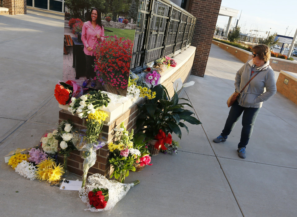 Photo - Thunder fan Kathy Medford of Midwest City looks at flowers she and others left in memory of Ingrid Williams, the wife of Oklahoma City Thunder assistant coach Monty Williams, before an NBA basketball game between the New Orleans Pelicans and the Oklahoma City Thunder outside of the Chesapeake Energy Arena in Oklahoma City, Thursday, Feb. 11, 2016. Ingrid Williams died Wednesday evening after being injured in a car crash Tuesday night. Photo by Nate Billings, The Oklahoman