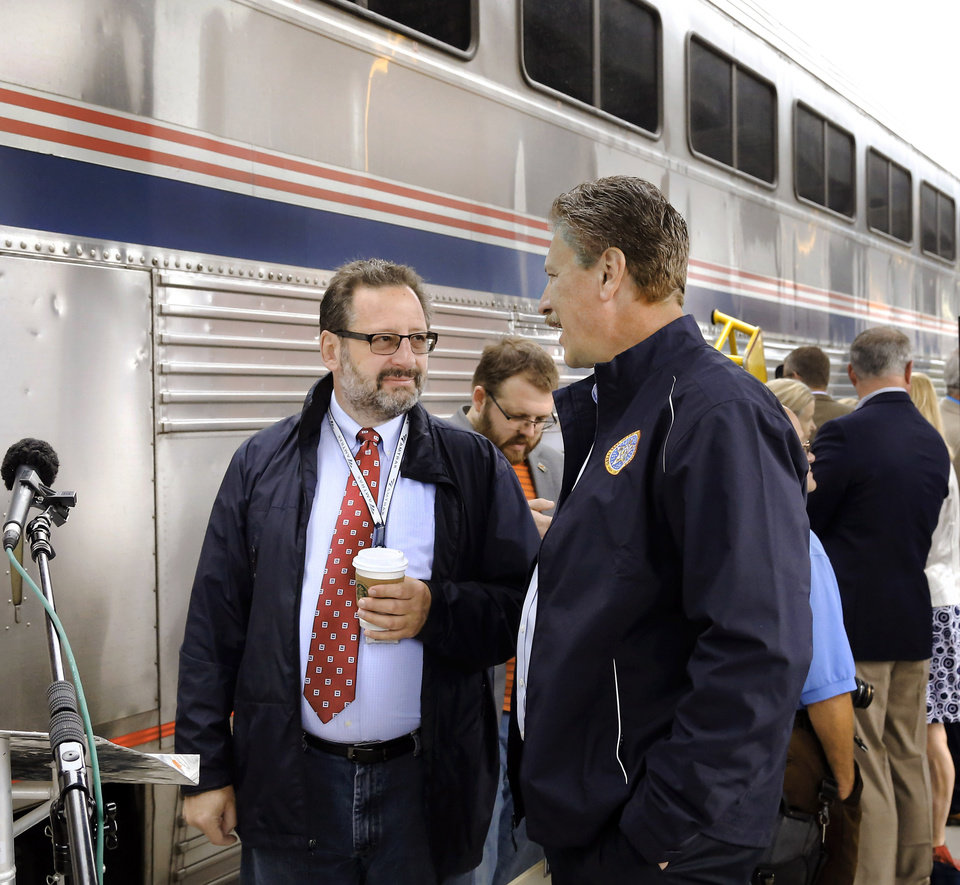 Photo - Marc Magliari, left, visits with Oklahoma Secretary of Transportation Tim Gatz  at Santa Fe Depot in downtown Oklahoma City Friday morning, June 14, 2019. Gatz and Magliari are among dignitaries and visitors who attended a brief ceremony at the train station marking the anniversary of the return of rail service to Oklahoma. The Heartland Flyer is celebrating its 20th year of serving rail passengers in Oklahoma and Texas. Magliari works for Amtrak where he is spokesman for   government affairs and corporate communications.  The daily service by Amtrak has carried more than 1.4 million passengers between Oklahoma City and Fort Worth during the past two decades. Originating its route on Oklahoma City, the Heartland Flyer connects to the Texas Eagle train in Fort Worth, which provides service to major cities including Dallas, Little Rock, St. Louis or Austin and San Antonio. [Jim Beckel/The Oklahoman]