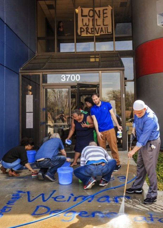 Photo -  A crew of volunteers works to remove racist and homophobic symbols and language spray-painted on the building that includes the offices of the Oklahoma Democratic Party located at 3700 Classen Boulevard in Oklahoma City, Okla. on Thursday, March 28, 2019.  Photo by Chris Landsberger, The Oklahoman