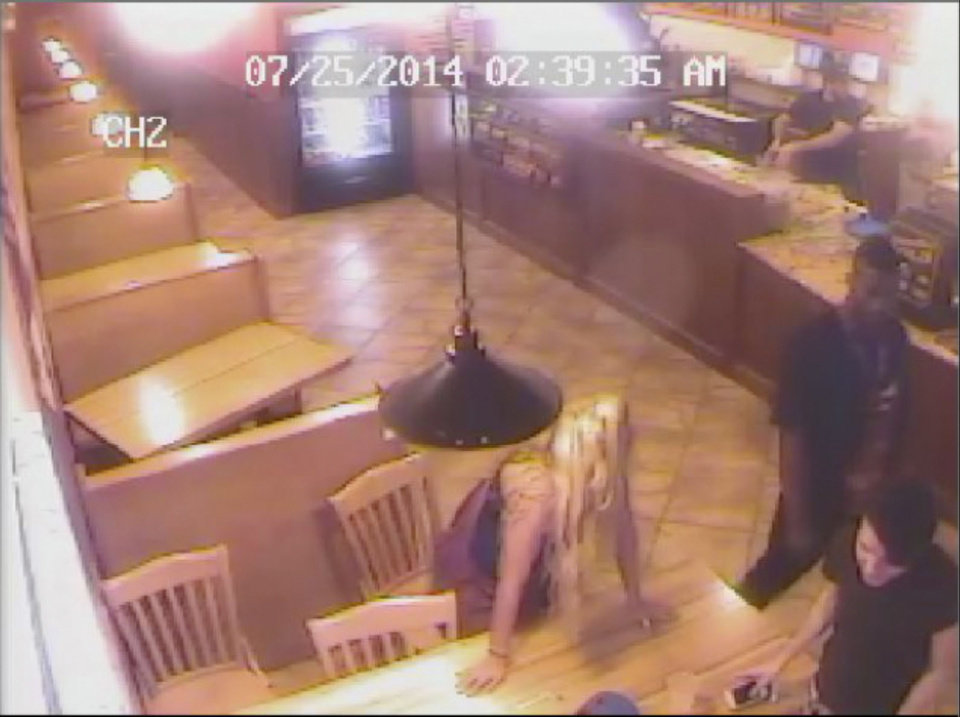 Photo - This screengrab from Pickleman's Gourmet Cafe surveillance video shows University of Oklahoma football player Joe Mixon, right, and Amelia Molitor, left, before an altercation between the two in the early morning on July 25, 2014 in Norman, Okla.