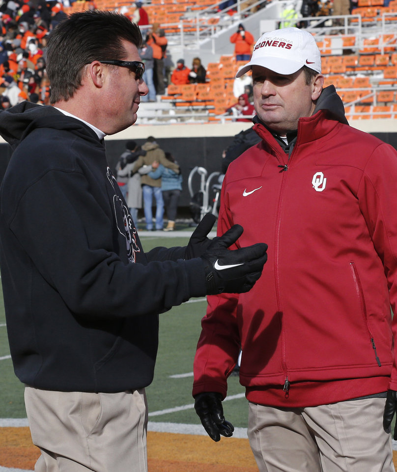 Photo - Oklahoma State head coach Mike Gundy, left, and Oklahoma head coach Bob Stoops, right, talk before the start of their NCAA college football game in Stillwater, Okla., Saturday, Dec. 7, 2013. (AP Photo/Sue Ogrocki)