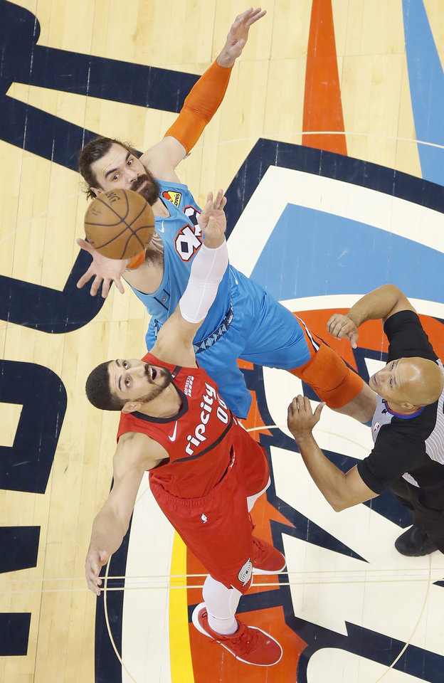 Photo - Oklahoma City's Steven Adams (12) and Enes Kanter (00) jump for the ball during the tip-off for Game 3 in the first round of the NBA playoffs between the Portland Trail Blazers and the Oklahoma City Thunder at Chesapeake Energy Arena in Oklahoma City, Friday, April 19, 2019. Oklahoma City won 120-108. Photo by Bryan Terry, The Oklahoman