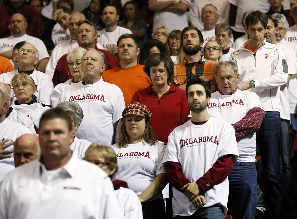 Photo - OU and OSU fans pause for a moment of silence to honor the ten men associated with the OSU men's basketball program who died in a 2001 plane crash, before the NCAA men's Bedlam basketball game between the Oklahoma State Cowboys (OSU) and the Oklahoma Sooners (OU) at Lloyd Noble Center in Norman, Okla., Monday, Jan. 27, 2014. Photo by Nate Billings, The Oklahoman