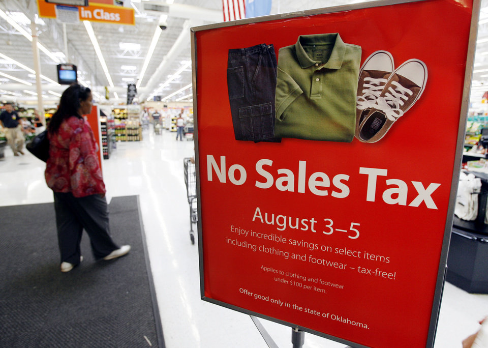 Photo - SALES TAX HOLIDAY: A sign advertises Oklahoma's tax-free weekend for back-to-school shopping, at the Wal-Mart Supercenter at 1808 Belle Isle Blvd. in Oklahoma City, Wednesday, August 1, 2007. By Nate Billings, The Oklahoman ORG XMIT: KOD