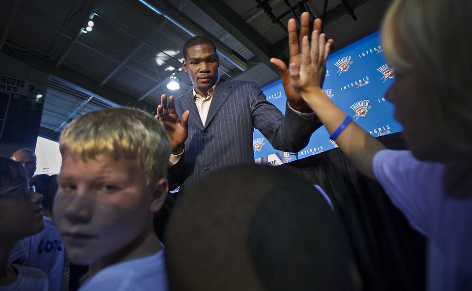 Photo - Kevin Durant greets basketball camp participants with high-fives after a press conference to officially announce Durant's  five-year contract extension to play for the Oklahoma City Thunder on Friday, July 9, 2010, in Oklahoma City, Okla.   Photo by Chris Landsberger, The Oklahoman