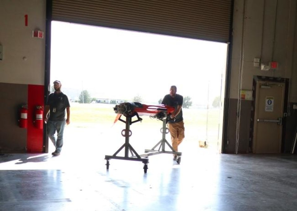 Photo -  Kratos employees move a target drone inside after testing its engine last year. [DOUG HOKE/THE OKLAHOMAN]