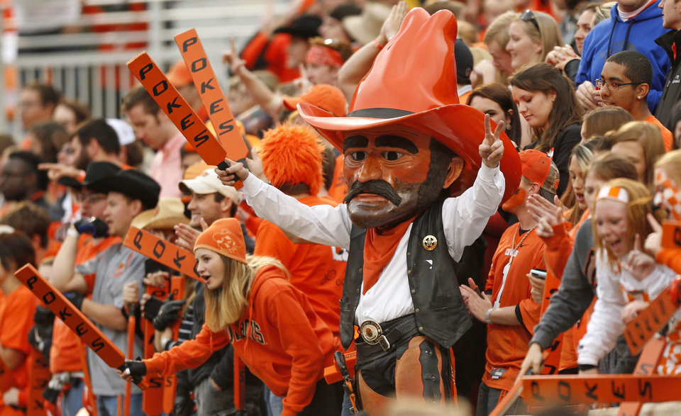 Photo - Pistol Pete holds a paddle with fans during a college football game between the Oklahoma State University Cowboys (OSU) and the Kansas Jayhawks (KU) at Boone Pickens Stadium in Stillwater, Okla., Saturday, Oct. 24, 2015. OSU won 58-10. Photo by Nate Billings, The Oklahoman