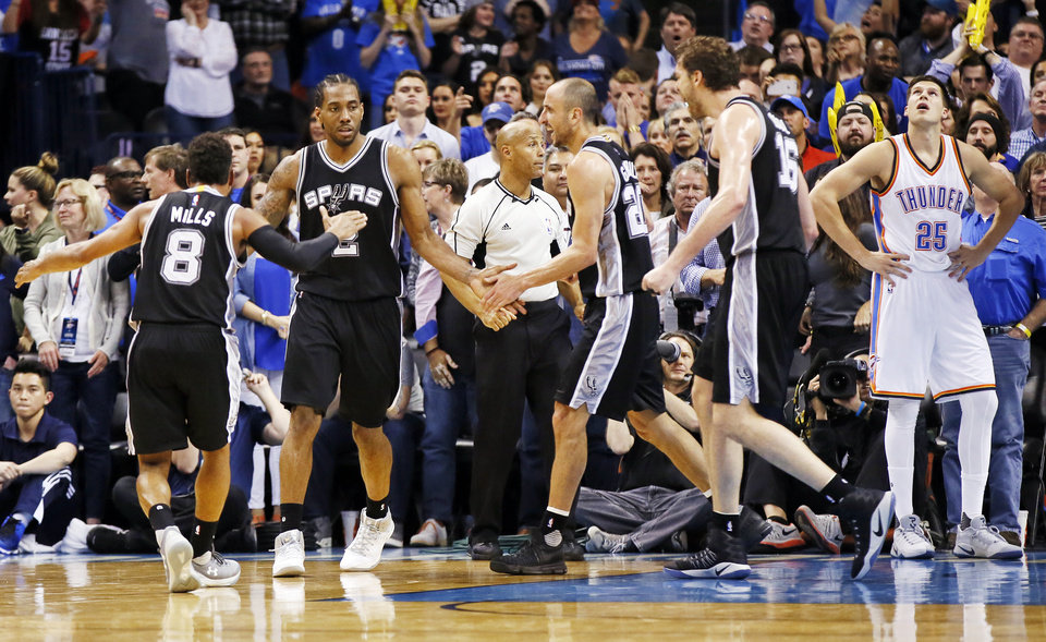 Photo - From left, San Antonio's Patty Mills (8), Kawhi Leonard (2), Manu Ginobili (20) ans Pau Gasol (16) celebrate near Oklahoma City's Doug McDermott (25) after Leonard made a shot and was fouled late in the fourth quarter of an NBA basketball game between the Oklahoma City Thunder and San Antonio Spurs at Chesapeake Energy Arena in Oklahoma City, Friday, March 31, 2017. San Antonio won 100-95. Photo by Nate Billings, The Oklahoman