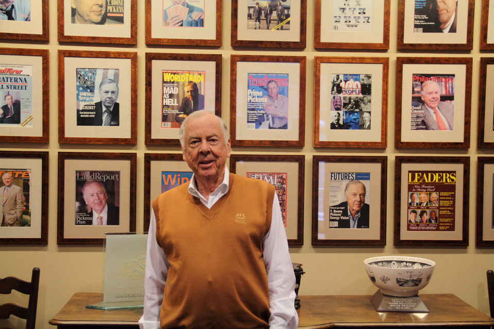Photo - T. Boone Pickens poses in front of his magazine covers at his home in Dallas, Texas, Wednesday, May 20, 2015. Photo by Adam Wilmoth, The Oklahoman