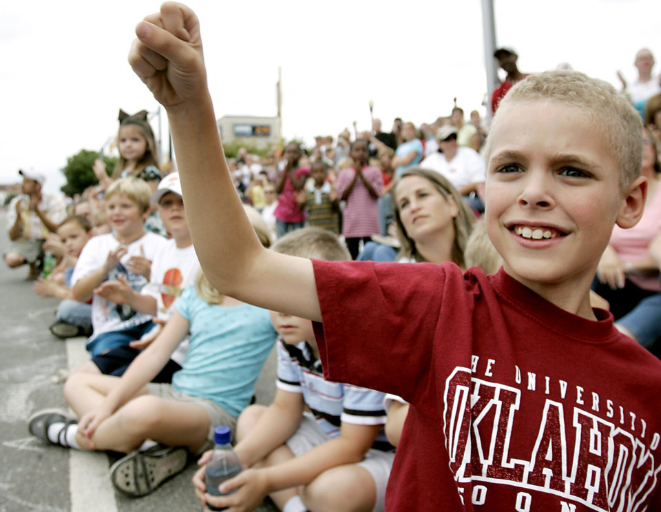 Photo - Morgan Dimon, age 9, pumps his fist as the Pride of Oklahoma Marching Band plays a song during the Oklahoma Centennial Parade in Oklahoma City on Sunday, Oct. 14, 2007. By John Clanton, The Oklahoman
