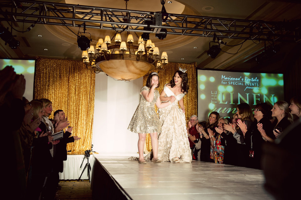 Photo -  Former Miss Oklahoma Kelsey Griswold and Miracle Child Keelie Garrett walk the runway at last year's Linen Runway Show. Photo provided