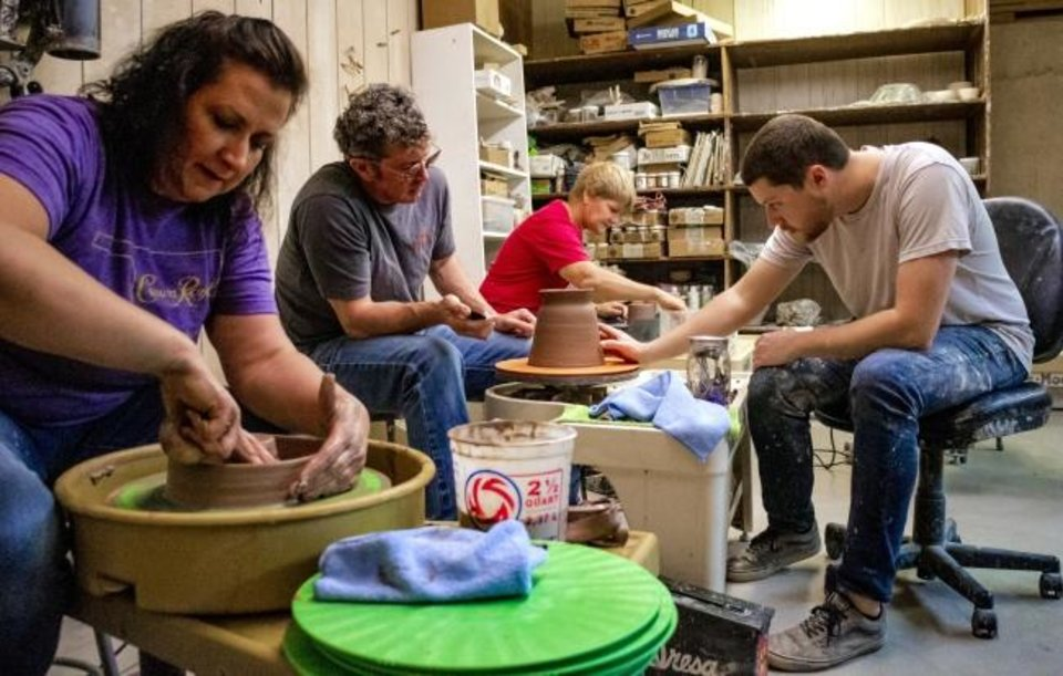Photo -  Taylor Dickerson, right, works with student Wade Smith in his pottery class.   [Chris Landsberger/The Oklahoman]