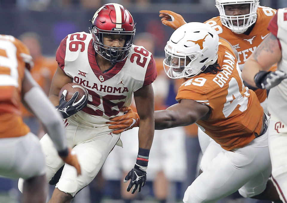 Photo - Oklahoma's Kennedy Brooks (26) Ta'Quon Graham (49) of Texas during the Big 12 Championship football game between the Oklahoma Sooners (OU) and the Texas Longhorns (UT) at AT&T Stadium in Arlington, Texas, Saturday, Dec. 1, 2018.  Oklahoma won 39-27. Photo by Bryan Terry, The Oklahoman