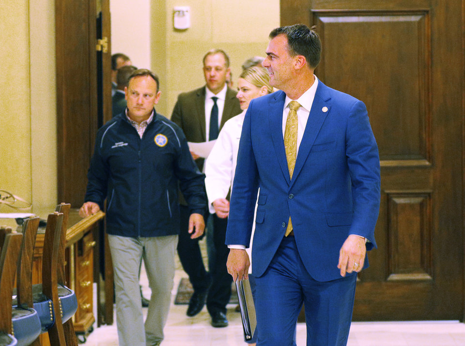 Photo - Gov. Kevin Stitt, Kayse Shrum and Jerome Loughridge leave the Governor's office heading to the Blue Room before the media briefing for the Governor's Solution Task Force to provide an update on Oklahoma's COVID-19 response in the Blue Room of the Capitol Wednesday, April 15, 2020.  [Photo by Doug Hoke/The Oklahoman]