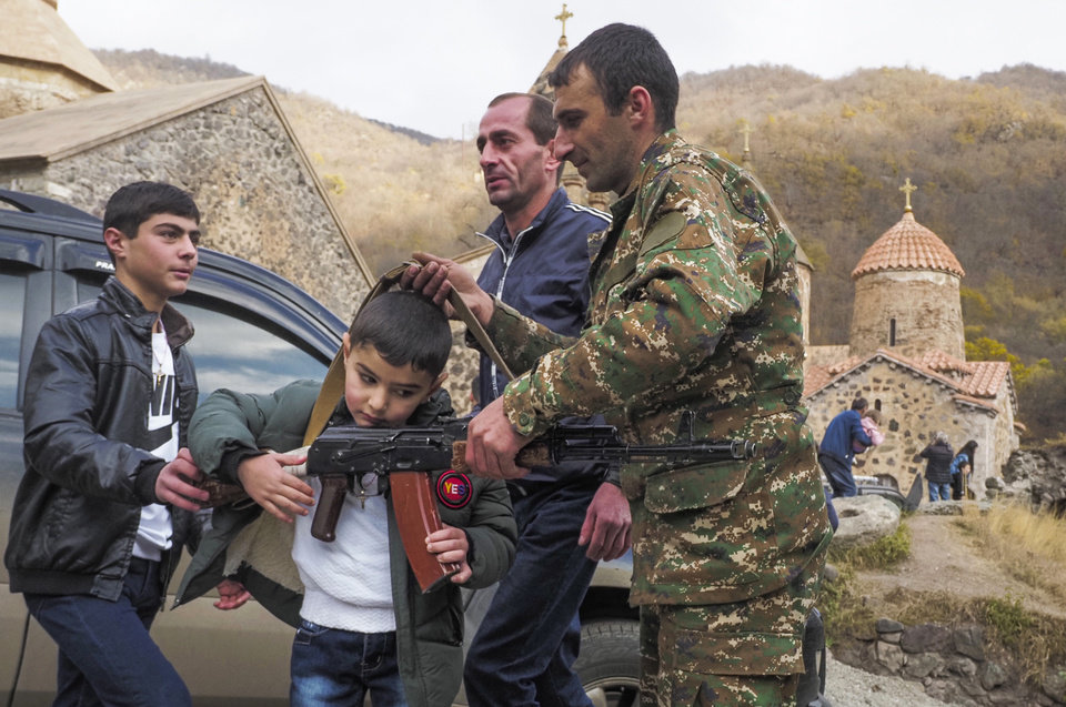 Photo -  People shows a Kalashnikov gun to a boy at the Dadivank, an Armenian Apostolic Church monastery dating to the 9th century, as ethnic Armenians leave the separatist region of Nagorno-Karabakh to Armenia, Saturday, Nov. 14, 2020. The territory is to be turned over to Azerbaijan on Sunday as part of territorial concessions in an agreement to end six weeks of intense fighting with Armenian forces. Hundreds of thousands of Azeris were displaced by the war that ended in 1994. It is unclear when any civilians might try to settle in Karvachar — which will now be known by its Azeri name Kalbajar — or elsewhere. (AP Photo/Dmitry Lovetsky)