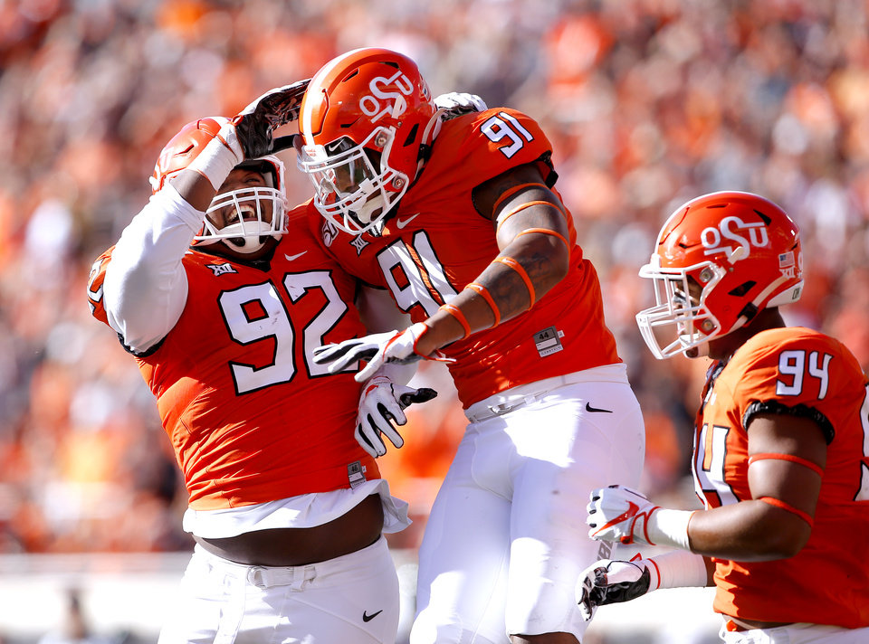 Photo - Oklahoma State's Cameron Murray (92), Mike Scott (91) and Trace Ford (94) celebrate a Scott sack in the second quarter during the college football game between Oklahoma State University and Baylor at Boone Pickens Stadium in Stillwater, Okla., Saturday, Oct. 19, 2019. Baylor won 45-27. [Sarah Phipps/The Oklahoman]
