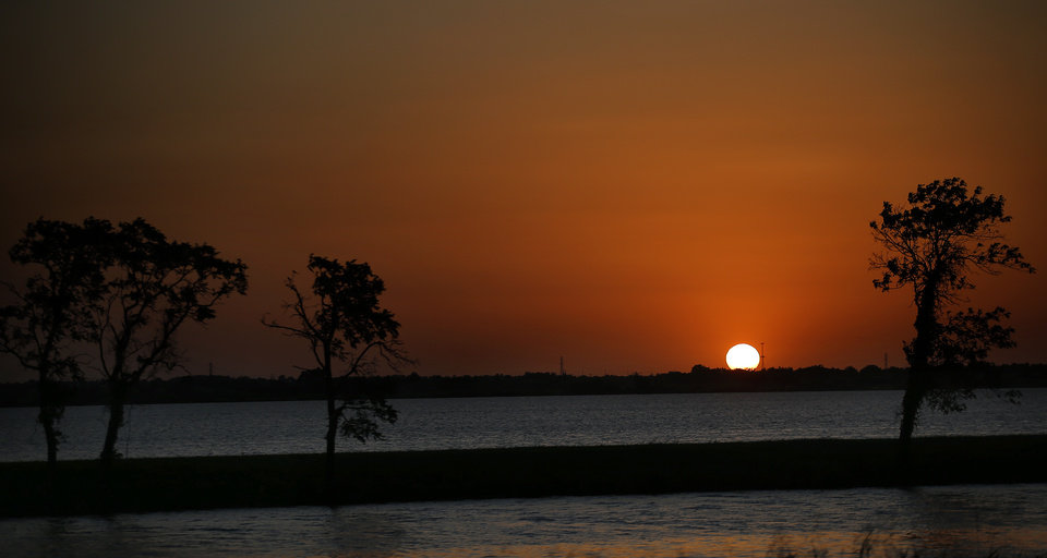 Photo - The sun sets at Lake Overholser in Oklahoma City, Friday, July 21, 2017. Photo by Sarah Phipps, The Oklahoman