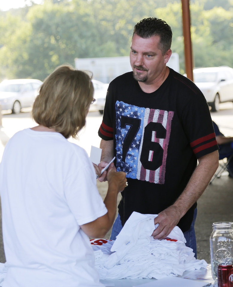 Photo - Michael Carlson buys Stop OTA tee shirts after the Victimsofiminentdomain.com rally at Choctaw Creek Park, in Choctaw, against the eastern Oklahoma county turnpike leg that the Oklahoma Turnpike Authority has proposed building Friday, August 12, 2016. Photo by Doug Hoke, The Oklahoman
