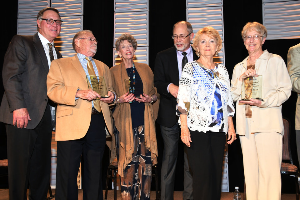 Photo - Individuals who have served as Whiz Kids volunteer tutors for 20 years or longer stand on stage at the recent Whiz Kids Oklahoma