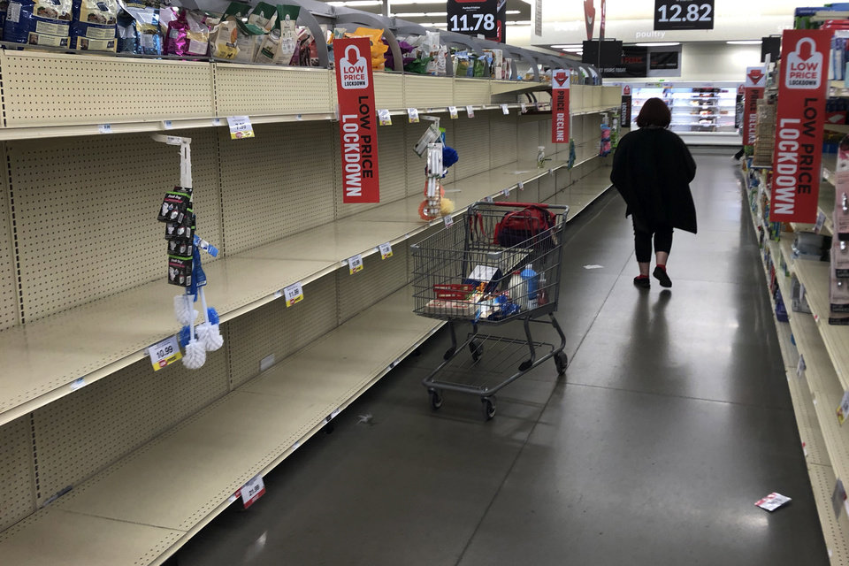 Photo -  A woman shops among empty shelves at a Hy-Vee food store Friday, March 13, 2020, in Overland Park, Kan. (AP Photo/Charlie Riedel)