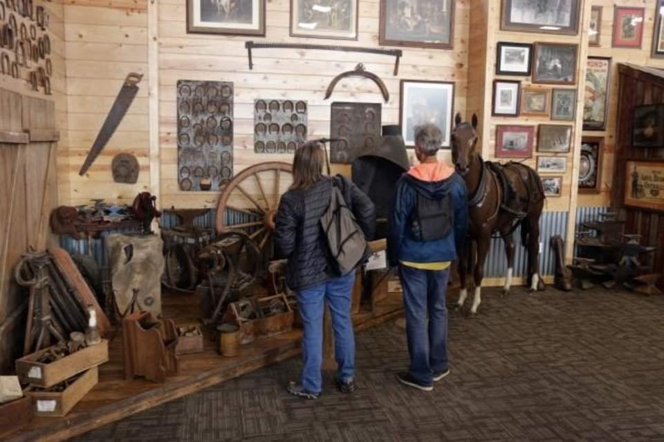 Photo -  People look at a display during Saturday's opening of the Museum of Horseshoeing in Stockyards City. [Doug Hoke/The Oklahoman]