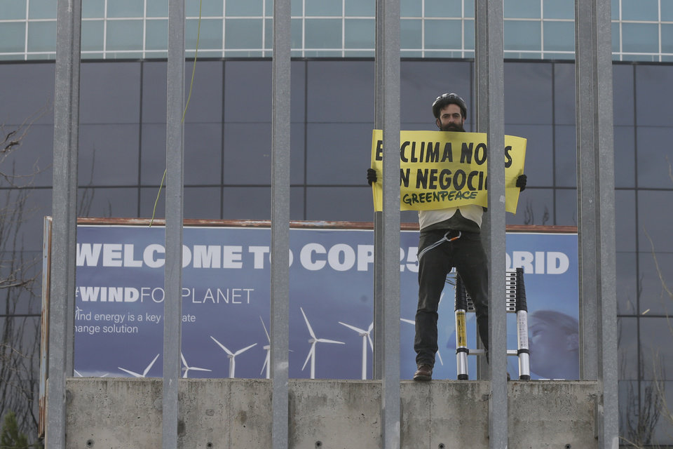 Photo -  A Greenpeace activist displays a banner reading 'The climate is not a business' outside the COP25 climate talks congress in Madrid, Spain, Friday, Dec. 13, 2019. The United Nations Secretary-General has warned that failure to tackle global warming could result in economic disaster. (AP Photo/Paul White)