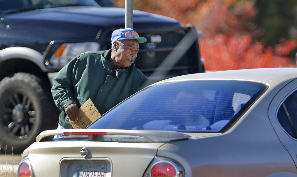 Photo -  A panhandler gets a handout at the intersection of Memorial and May Avenue in Oklahoma City, Friday October, 6 2015. Photo By Steve Gooch, The Oklahoman