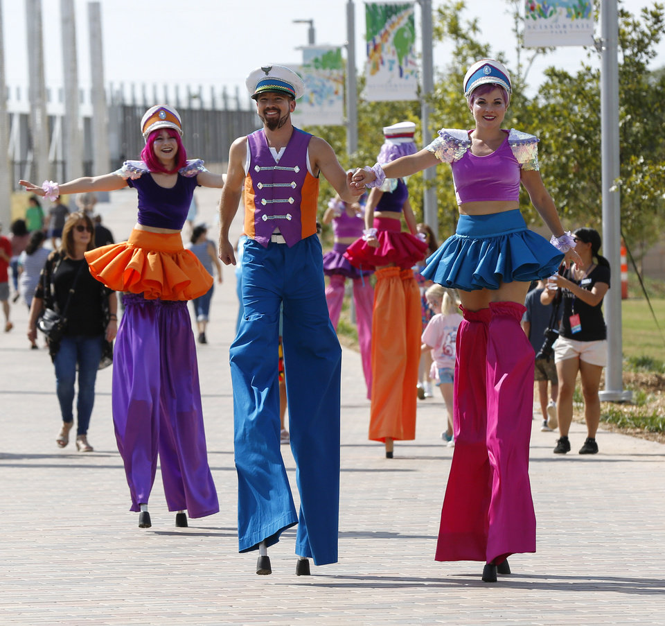 Photo - Performers from Inspyral Circus walk through the park during the grand opening weekend of Scissortail Park in Oklahoma City, Saturday, Sept. 28, 2019. [Nate Billings/The Oklahoman]