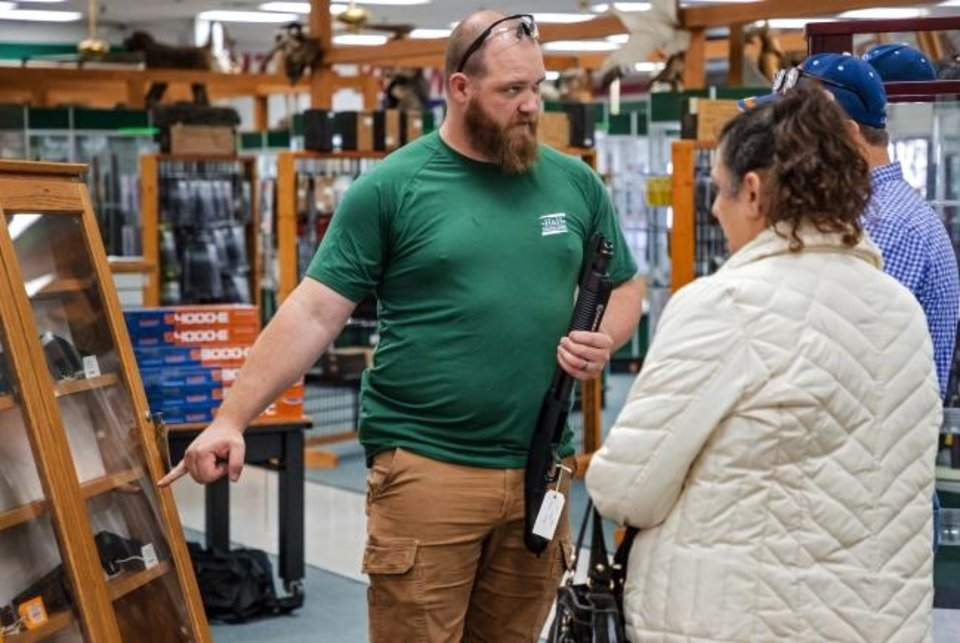 Photo -  H&H Shooting Sports employee Charles Duvall helps customers as they shop for a gun at H&H Shooting Sports on March 18.  [Chris Landsberger/The Oklahoman]