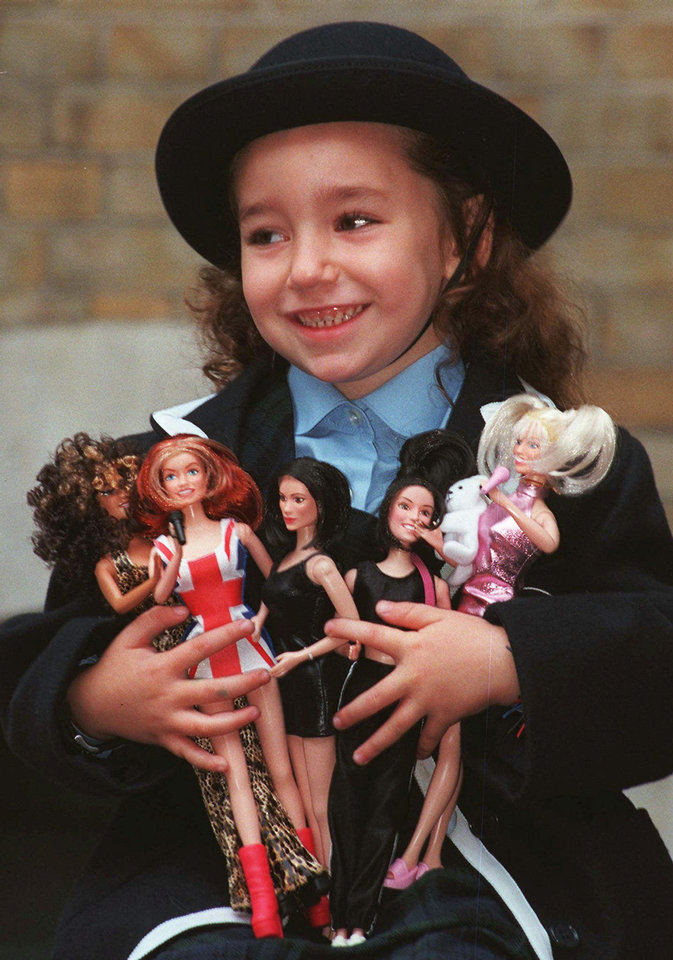 Photo - Jodie Loftus, 4, holds an armload of the Spice Girls dolls when they were first unveiled at a fair of Christmas toys Oct. 16, 2007 in London. (AP Photo/Lynne Sladky)  LYNNE SLADKY - AP