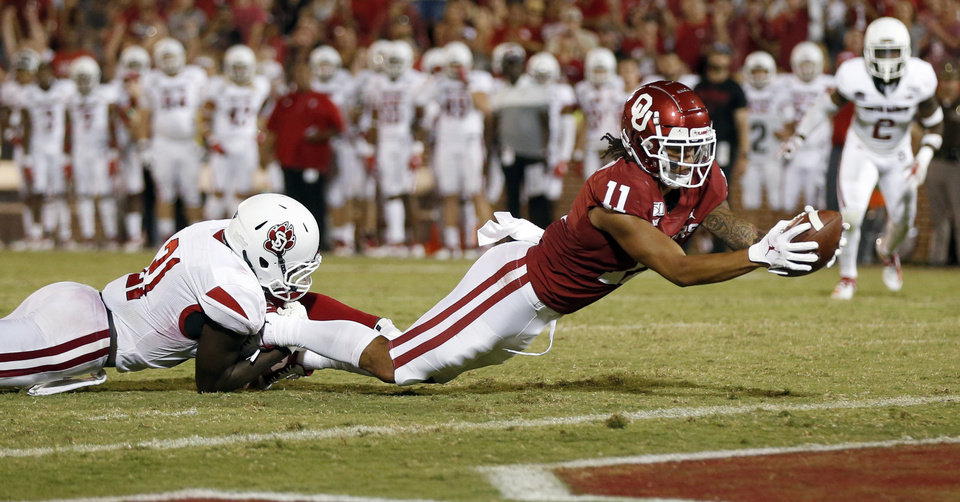 Photo - Oklahoma's Jadon Haselwood (11) scores a touchdown as South Dakota's Phillip Powell (21) pull him down in the third quarter during a college football game between the Oklahoma Sooners (OU) and South Dakota Coyotes at Gaylord Family - Oklahoma Memorial Stadium in Norman, Okla., Saturday, Sept. 7, 2019. [Nate Billings/The Oklahoman]