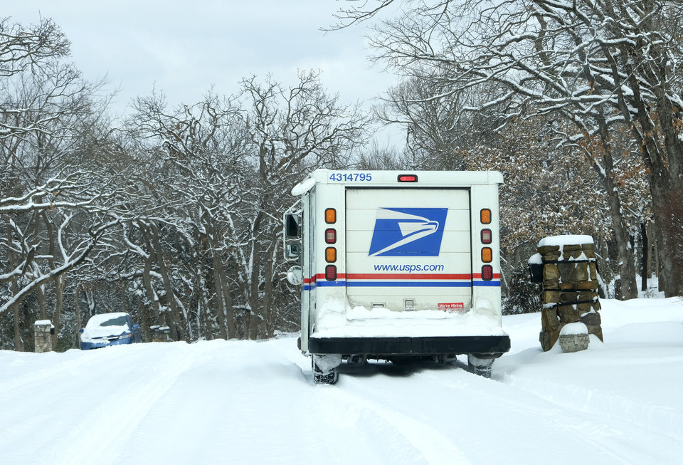 Photo - The Postal Service truck has chains to deliver the mail to a neighborhood in Edmond Wednesday, February 17, 2021. [Doug Hoke/The Oklahoman]
