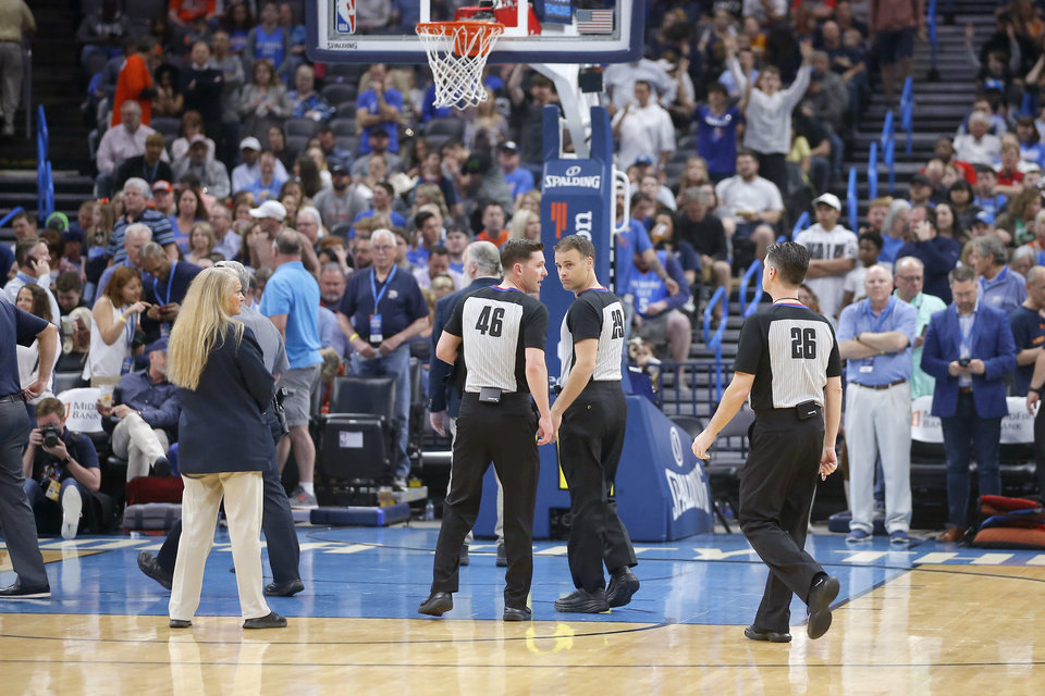 Photo - Officials leave the court before an NBA basketball game between the Oklahoma City Thunder and the Utah Jazz was postponed at Chesapeake Energy Arena in Oklahoma City, Wednesday, March 11, 2020. [Bryan Terry/The Oklahoman]