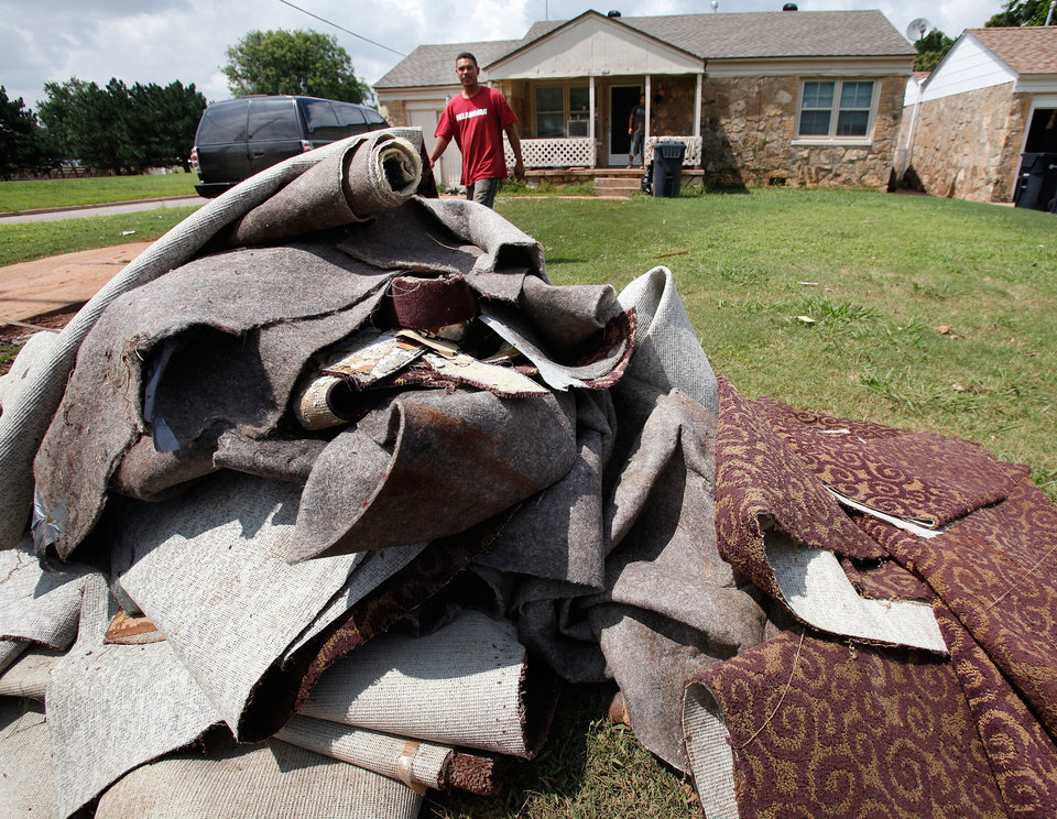 Photo - Carpet removed from this house at SE 37 and Broadway. Residents cleaned homes and yards in the area near Lightning Creek in south Oklahoma City, Friday, July 9, 2010. Heavy rains last night caused the  creek to overflow its banks, flooding the areas on both sides of the creek.  Staff Photo by Jim Beckel , The Oklahoman
