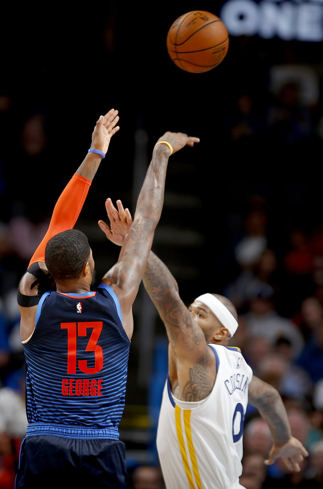 Photo - Oklahoma City's Paul George (13) shoots over Golden State's DeMarcus Cousins (0) during the NBA basketball game between the Oklahoma City Thunder and the Golden State Warriors at Chesapeake Energy Arena,  Saturday, March 16, 2019. Photo by Sarah Phipps, The Oklahoman