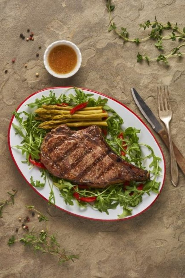 Photo -  Grilled rib-eye is accented with local arugula and a glaze made from Oklahoma-made ingredients. [Photo provided]