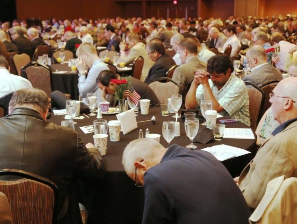 Photo -  Attendees bow in prayer during the 2016 CBMC Metro Prayer Breakfast at the Cox Convention Center in Oklahoma City. [Oklahoman Archives]