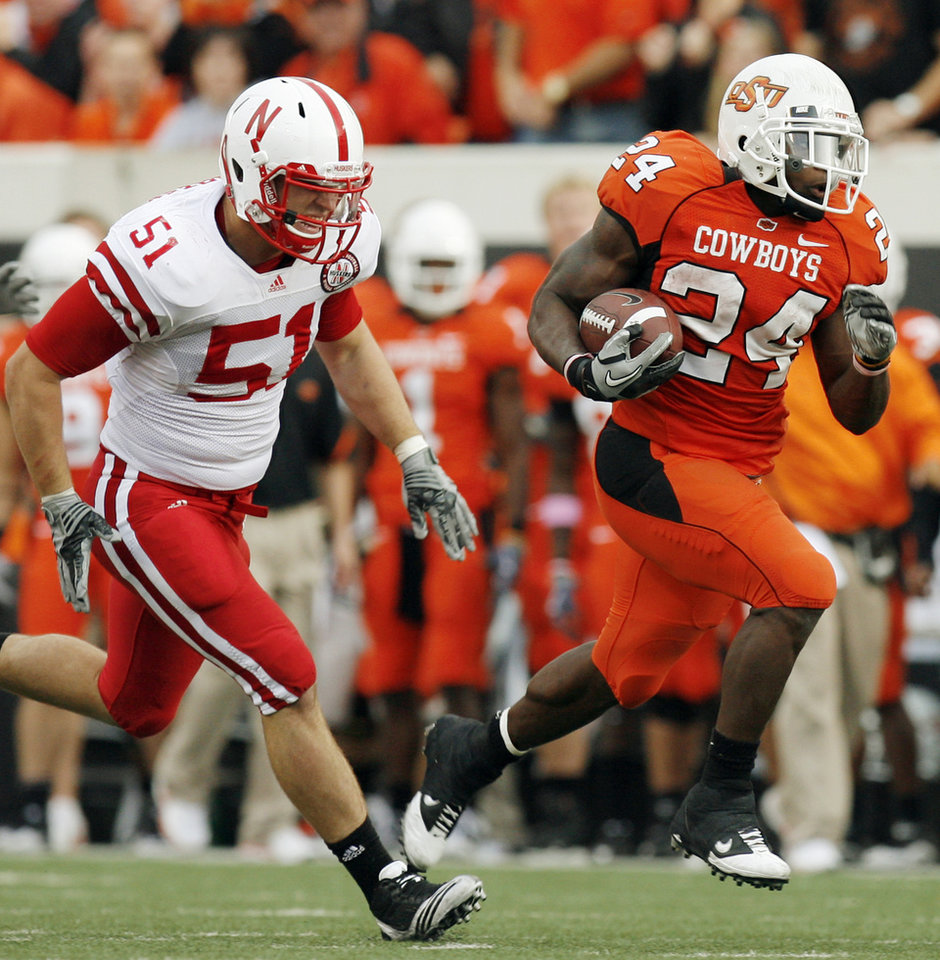 Photo - OSU's Kendall Hunter (24) runs away from Will Compton (51) of Nebraska in the third quarter during the college football game between the Oklahoma State Cowboys (OSU) and the Nebraska Huskers (NU) at Boone Pickens Stadium in Stillwater, Okla., Saturday, Oct. 23, 2010. Nebraska won, 51-41. Photo by Nate Billings, The Oklahoman