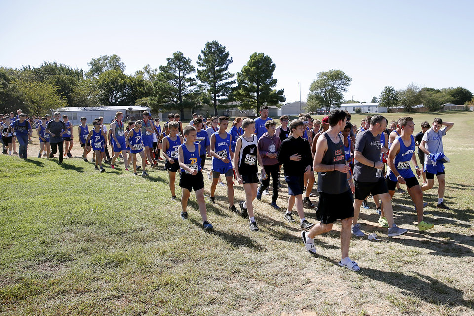 Photo - Newcastle runner Caleb Freeman, who was injured in a 2017 car crash, is followed by a large crowd as he runs a cross country race at Carl Albert in Midwest City, Okla., Tuesday, Oct. 8, 2019. This was Caleb Freeman's first cross country race since getting injured in a 2017 car wreck. [Bryan Terry/The Oklahoman]