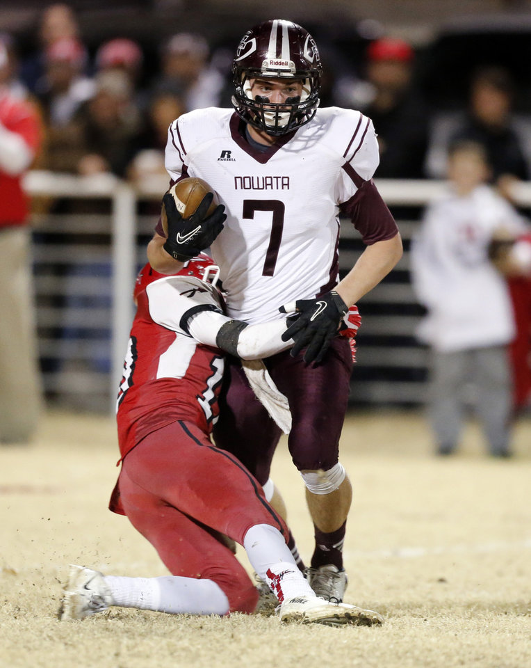 Photo - Nowata's Billy Davis is stopped by Brody Harmon as the Nowata Ironmen play the Washington Warriors in high school football on Friday, Nov. 28, 2014 in Washington, Okla. Photo by Steve Sisney, The Oklahoman